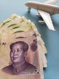 chinesische Banknoten, weißes Plastikflugzeug und blauer Hintergrund lizenzfreies stockfoto