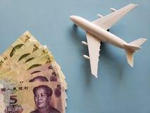 chinesische Banknoten, weißes Plastikflugzeug und blauer Hintergrund stockbilder