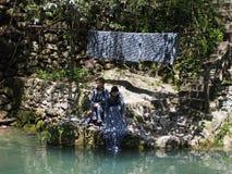 Chinesische Dame, die sie Kleidung in dem Fluss am lokalen Landhaus wäscht lizenzfreies stockfoto
