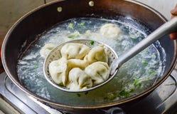 Chinesische Familie, die gekochte Mehlklöße im Wok kocht Stockfotos