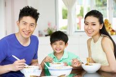 Chinesische Familie, die zu Hause sitzt, eine Mahlzeit essend Stockfotografie