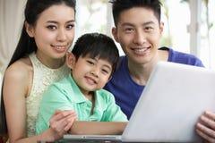 Chinesische Familie, die zu Hause unter Verwendung des Laptops sitzt Lizenzfreie Stockfotos