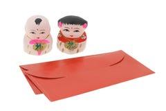 Chinesische Figürchen des neuen Jahres und rote Pakete stockfoto