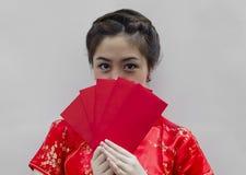 Chinesische Frau, die rote Beutel anhält Stockbild