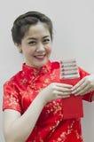 Chinesische Frau, die rote Beutel anhält Stockbilder