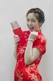 Chinesische Frau, die rote Beutel anhält Stockfotografie