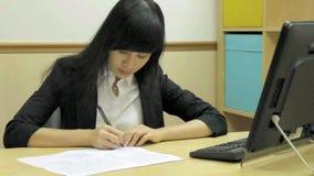 Chinesische Geschäftsfrau am Schreibtischschreiben stock footage