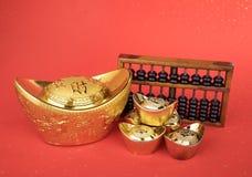 Chinesische Goldbarren- und -abakusmittelsymbole des Reichtums stockfotos