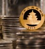 Chinesische Goldmünze unter Stapeln der Silbermünzen Stockfoto