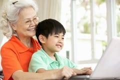 Chinesische Großmutter und Enkel, der Laptop verwendet Stockfotos
