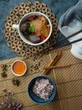 Chinesische Hühnersuppe in einer weißen Schale, verziert mit chinesischen Shiitakepilzen, goji Beeren, Hühnerblut und Korianderbl lizenzfreie stockfotos