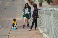 Chinesische Kinder, die auf dem Bürgersteig spielen Lizenzfreies Stockbild