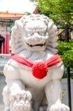 Chinesische Löwestatue und rotes Band im chinesischen Tempel Stockfotografie