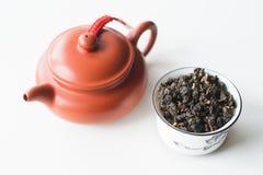 Chinesische Lehmteekanne und -schüssel mit Tee auf einem weißen Hintergrund Stockbild