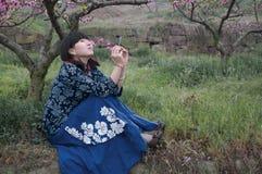 Chinesische Mädchen- und Pfirsichblumen Stockbild