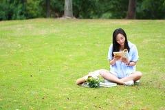 Chinesische Mädchenlesung im Park Blonde schöne junge Frau mit Buch sitzen auf dem Gras Lizenzfreie Stockfotografie