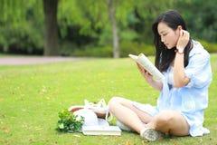Chinesische Mädchenlesung im Park Blonde schöne junge Frau mit Buch sitzen auf dem Gras Stockfotos