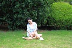 Chinesische Mädchenlesung im Park Blonde schöne junge Frau mit Buch sitzen auf dem Gras Lizenzfreies Stockfoto