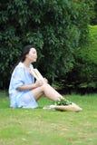 Chinesische Mädchenlesung im Park Blonde schöne junge Frau mit Buch sitzen auf dem Gras Stockbild