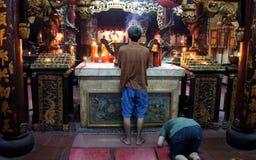 Chinesische Männer, die innerhalb eines Tempels beten Lizenzfreies Stockfoto