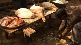 Chinesische Männer verbreiten Salz gleichmäßig auf dem Schinken und bedrängen es wiederholt zur Herstellung von Nuodeng-Schinken  stockbild