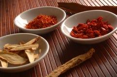 Chinesische Medizin und Kräuter in den Schüsseln auf Bambusmatte Lizenzfreie Stockfotografie