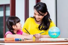 Chinesische Mutter, die Schulhausarbeit mit Kind tut Stockfotos
