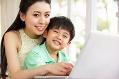 Chinesische Mutter und Sohn, der Laptop verwendet Stockbild