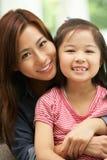 Chinesische Mutter und Tochter, die auf Sofa sitzt Lizenzfreies Stockfoto