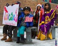 Chinesische neues Jahr-Parade mit Kind-wellenartig bewegender Markierungsfahne Stockfoto