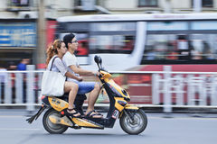 Chinesische Paare auf einem elektrischen Fahrrad O Stockfotos