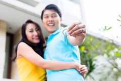Chinesische Paare, die Schlüssel zu ihrem neuen Haus zeigen Lizenzfreies Stockbild
