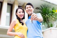 Chinesische Paare, die Schlüssel zu ihrem neuen Haus zeigen Stockbild