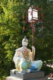Chinesische Statue, die eine Laterne hält Stockbild