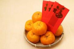 Chinesische Tangerinen im Korb mit roten Paketen des Chinesischen Neujahrsfests - Reihe 2 Lizenzfreie Stockfotografie