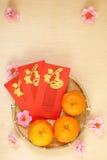 3 chinesische Tangerinen im Korb mit roten Paketen des Chinesischen Neujahrsfests - Reihe 4 Stockbilder