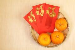 3 chinesische Tangerinen im Korb mit Rotpaketen des Chinesischen Neujahrsfests Stockbild