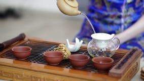 Chinesische Teezeremonie, ein Mädchen in einem blauen Kleid, gießt wohlriechenden Tee durch ein Sieb in den Kessel stock video