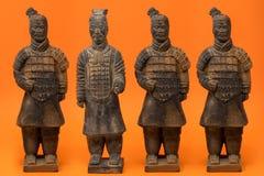 4 chinesische Terrakottakrieger gegen eine Leuchtorange b lizenzfreies stockfoto
