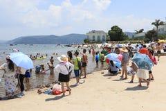 Chinesische Touristen auf einem Strand des Fuxian Sees in Yunnan, der thid tiefste See in China Es ist zwischen dem Kapital lokal Stockbilder