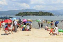 Chinesische Touristen auf einem Strand des Fuxian Sees in Yunnan, der thid tiefste See in China Es ist zwischen dem Kopf lokalisi Stockfoto