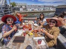 Chinesische Touristen, die Hummer essen Stockbild