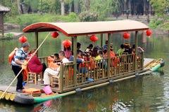 Chinesische Touristen nehmen ein altes Boot auf einem Fluss oder einem kleinen See Stockbild