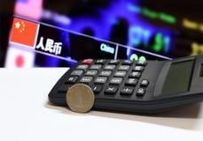 Chinesische Yuan-Münzen auf Rück-CNY-Bankadresse ZHONGHUA RENMIN YINHANG auf Chinesisch auf weißem Boden und Taschenrechner mit d stockfoto