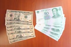 Chinesische Yuans durch fünfzig (50), Dollar Vereinigter Staaten durch (10) Bezeichnung zehn sind auf einer Tabelle vor einer Rei Stockbild