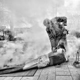 Chinesischer älterer Mann, der traditionelle Maispopkornmaschine laufen lässt Stockbilder