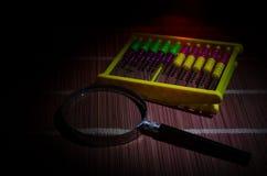 Chinesischer Abakus und Lupe, Geschäftskonzept auf einem dunklen Hintergrund Lizenzfreie Stockfotografie