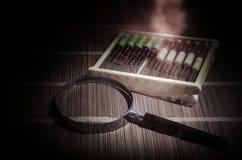 Chinesischer Abakus und Lupe, Geschäftskonzept auf einem dunklen Hintergrund Stockfotos