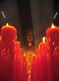 Chinesischer Buddha im Rauche mit roten Kerzen Stockfotos