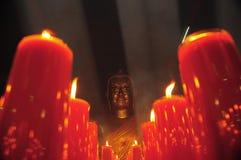 Chinesischer Buddha mit roten Kerzen Lizenzfreie Stockfotos